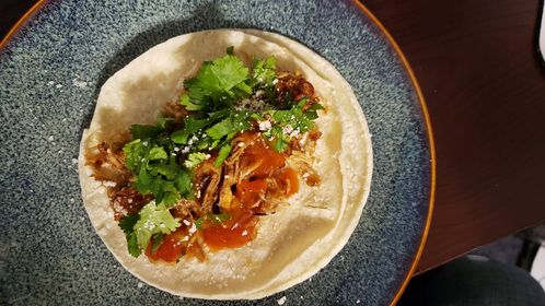 Bourbon Chicken Taco on White Corn Tortilla topped with Mango Habanero Salsa, Chopped Cilantro, and Cotija Cheese